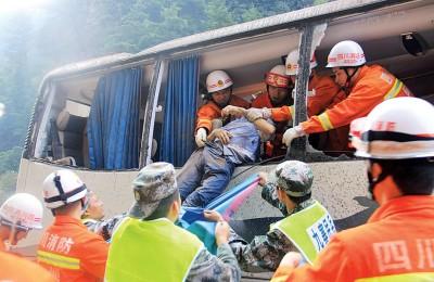 巨石滚落,适砸在了万先生乘坐的游览巴车尾。(法新社照片)