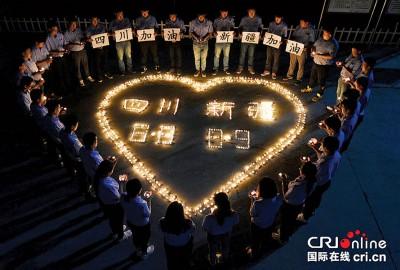 民众用蜡烛组成心形字样祈福,希望灾民早日渡过难关。