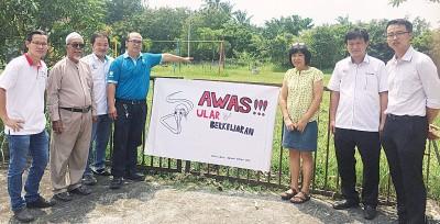 当地社委会在游乐场所挂上毒蛇出没的警告布条,右为李凯伦。