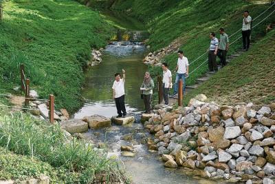 曹观友(左)在水利灌溉局官员及新港德沙丽亚居民协会成员的陪同下,巡视已完工的新港河。
