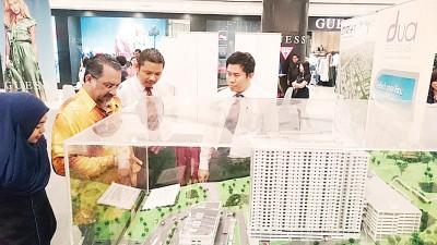 佳日星(左)于槟州可负担房屋展览首天走访参展摊位。
