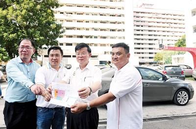 黄伟益(左起)、刘敬亿、曹观友及林峰安展示,建议在五条路组屋区篮球场休闲地兴建多层多用途停车场的草图。