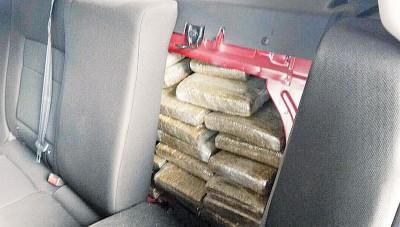 执法官员在后坐椅背与音响系统之间发现了大批块状疑似大麻的毒品。
