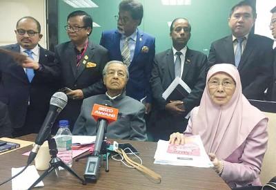 """马哈迪(左)指出,内陆税收局调查其儿子莫尼扎公司乃政府权力,但他也揶揄,政府的权力就是""""滥权""""。右为旺阿兹莎。"""