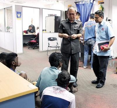 安华(站者左)在办事处检查其中1名嫌犯的身份证。