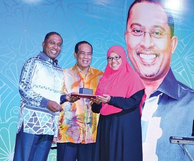 歌唱比里(左)当霹州秘书阿都布哈哈的伴随下颁发奖励金予退休公务员。