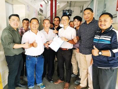 关庆华(左4)移交有关文件予刘火炎(左2),刘敬亿州议员(左1)、林锋安(后排左1)、依兹哈(右1)、沙鲁尔(右2)等人陪同见证。