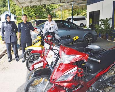丹尼尔(中)展示被充公的摩托车。