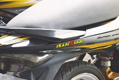 摩托车身贴着『我们不快』(KAMI X LAJU)贴纸。