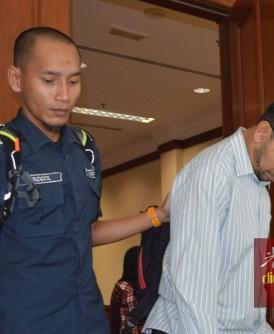 关税局人员押送被告莫哈末纳西尔(右)离开法庭。