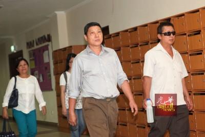 被告曹德良(右2,译音)与亲友离开法庭,从容面对媒体镜头。