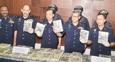 阿斯里(右2)向媒体展示起获的大麻毒品,左2为刑事调查主任米欧。