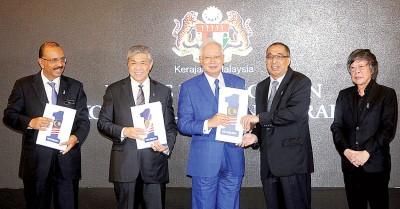 """首相(受)每当副首相(左2)陪伴下推介""""一个马来西亚我之国度""""表明。"""