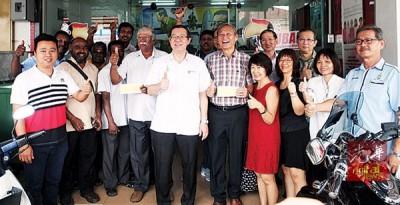 林冠英(前左6)移交拨款予P.克斯南(左5)及林旭辉(前右5)时,众人竖起拇指赞好!