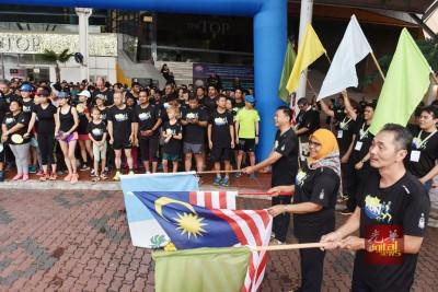 左起郑来兴、麦慕娜和陈永德,一起为是场5公里跑挥旗。