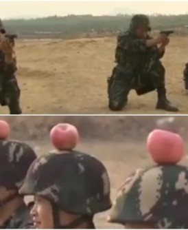 3名解放军进行超高危险射击训练,用手枪射击坐在约20米外的同僚头盔上的苹果。