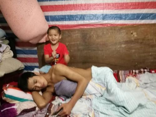5岁的小羽给瘫痪在床的父亲按摩敲背、照顾起居饮食。