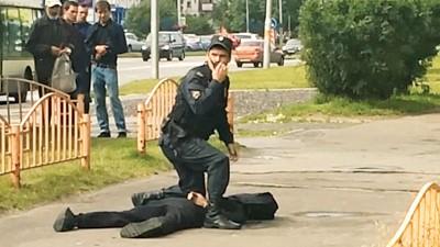 穿黑衣的嫌犯躺在地上,同名警力上前跨过前者身上,执对讲机请求支援。