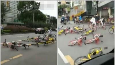 成都一名女子因感共享脚车堆满巴士站,于是将脚车扔到路中阻碍行车。