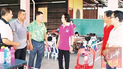 锺咏江(左1)与理事会成员,向陈彩瑛了解首天上课情况。