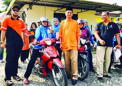 法依兹(中)频走访以马来选民居多的选区。