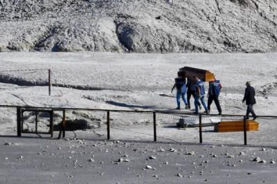 救援人员用帆布遮盖死者遗体。