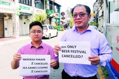 """黄伟益(右)和王宇航举起标语,诘问""""为何只有啤酒节""""遭禁?"""