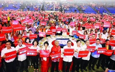 """敦马哈迪夫妻(左4跟5)跟林冠英(左6自)、曹观友与林吉祥一样多行动党领袖共在晚宴上和赴宴民众共同举起""""欲联盟""""海报。"""