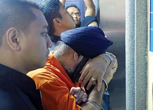 被告被带上庭时,以手遮脸逃避摄影镜头。