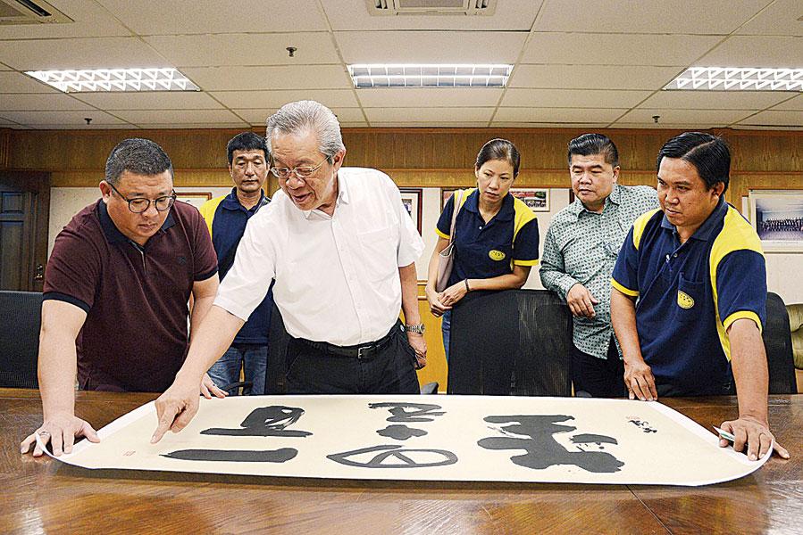 江真诚(左2)讲解作品的含义,王浩源(左)、赵惠坤(右起)、王益辉及林秀英仔细聆听。