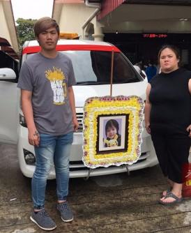 """刘德安(左)及李恩怡在灵车前,与小锦鸿拍摄最后的""""全家福""""。"""