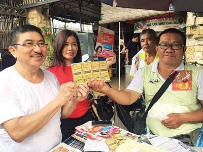 残疾人士林振利(右)是大彩公司彩票售卖员之一,他移交100张新款彩票给一名傅姓顾客(左),左2为洪彩凤。