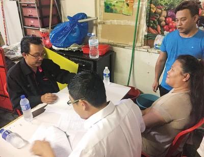 吉隆坡福利局官员阿兹哈依斯迈(左)协助陈丽丽(右)填写残障人士福利金申请表格。