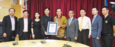 曾玉良和林翠薇(左3和左4)为林冠英(左5)当展示所取得健力士世界纪录证书。
