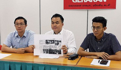 """黄勇靖(中)展示""""槟城街头美食节""""达15万人出席的报道,左为许保忠及黄志毅。"""