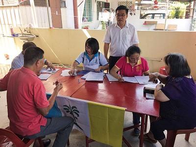 """黄汉伟(站者)于周一在天德园花园设立柜台,协助该区住宅区的灾民申请""""915水灾紧急援助金""""。"""