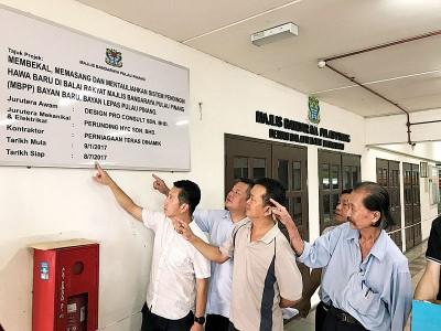 胡栋强指出槟岛市政厅宣布峇央峇鲁巴刹民众会堂的提升工程逾有9个月,却不见有任何动工现象。左2起为邱显昌、陈建  强木、许翔茗及张云丰。