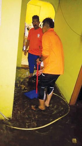 民防局派员协助灾民清洗屋子。