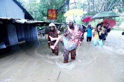 消拯员涉水把被行动不便的年迈老妇抱出。