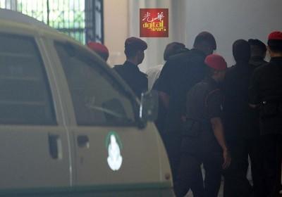 安华(白衣者)被狱警带到司法宫供证。