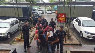 男被告从警车上被押入法庭。
