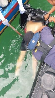 海事执法人员将遗体捞出海面。