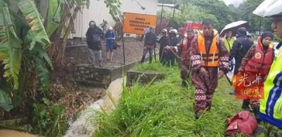 拯救人员在搜查被急流冲走的女摩托车骑士。