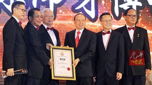 纳吉(左3)颁发福联会永久荣誉总会长委任状予林伟才(左4);左起刘国泉、邱财加、郑今智及陈长兴。