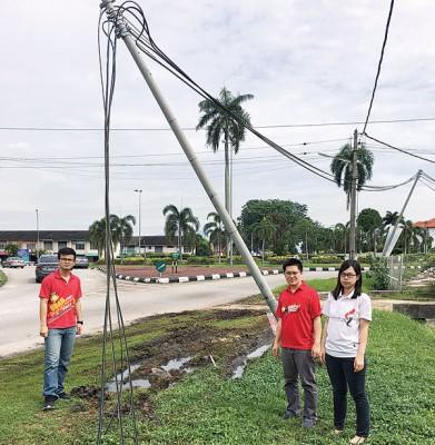 黄家和(中)连同崔慈恩(右)及张迪翔视察怀疑被大型车辆撞毁的电柱。