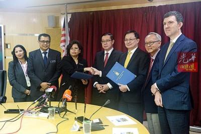 莎鲁(左3)和孙明福交换已签署合约,并由林冠英(左4)、董志兴和约翰等人见证。