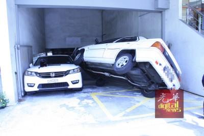 华妇疑因刹车失灵,直接撞上入口铁闸,之后翻覆压到停在一旁的轿车。