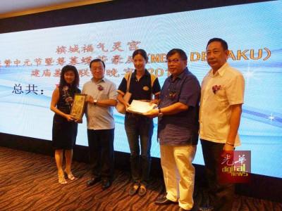 张誉发(右2)移交义款予大同建委会代表,左为总务林金水(左2)从街区代表郭燕美手中接领纪念品。