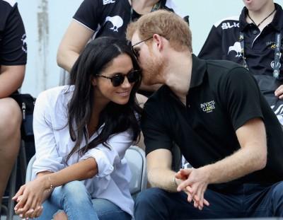 哈里不时在女友耳边轻语。(法新社照片)