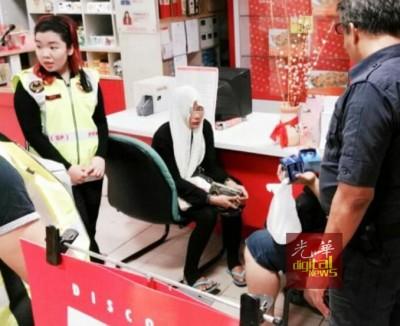 ?隰偷窃美容品的女子被捕后,等待送交警方发落。